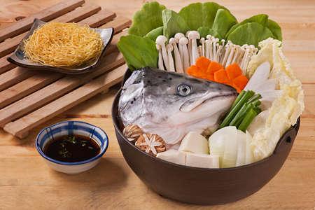 Hot pot de tête de saumon aux champignons, carottes, tofu, chou et nouilles séchées sur table en bois