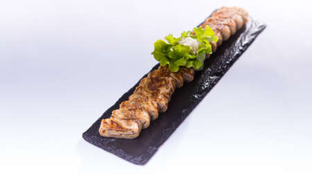 Sliced pork rolls with herbs on black rock plate Stock Photo
