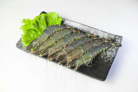 Fresh tiger shrimp with lettuce on black plate on white background Standard-Bild