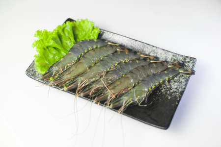 Fresh tiger shrimp with lettuce on black plate on white background Archivio Fotografico