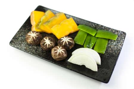Fresh vegetables with onion, mushroom, chili and pumpkin on black plate