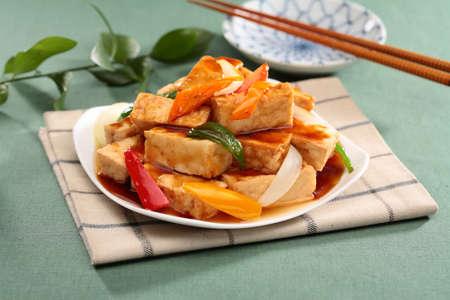흰 접시에 식탁보에 칠리와 양파 튀김 두부 뜨거운 물 스톡 콘텐츠