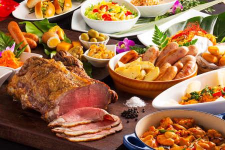 Table de nourriture avec boeuf grillé, saucisses, pâtes, tomates frites, poulet, poivrons, herbes et salade