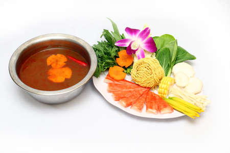 crab pot: Vietnamese spicy hot pot with mushroom, corn, cabbage, crab tempura, carrot and dried noodle on white background