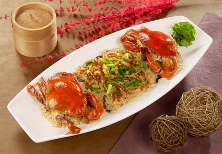 Cherry red crab glutinous rice with fried baby shrimps on white plate Stock Photo