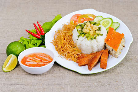 Special broken rice with fish sauce, lemon, fried pig skin, sliced cucumber and chili on white plate in Vietnam Standard-Bild