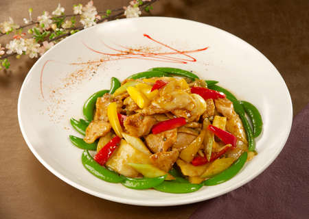 fricassee: Sauteed green peas with chicken and chili on white plate in restaurant