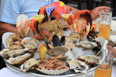 Seafood buffet with fresh oysters, clams, crabs, shrimps, snails, lobsters and beer in restaurant