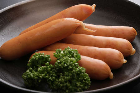 Raw pork sausages with cumin on big black pan Stock Photo