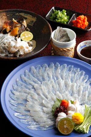 pez globo o fugu Wakasa filete fino en un gran plato con limón, salsa, wasabi y hierbas