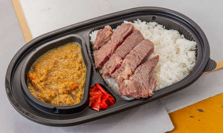 rajma: Beef steak curry with fried tempura, chili and plain rice in bento box Stock Photo