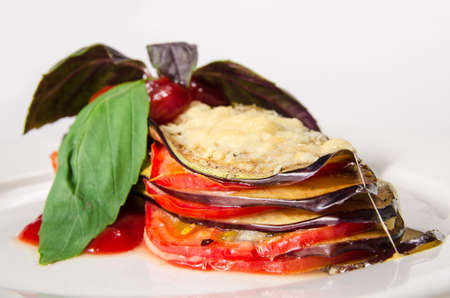 Fried sliced eggplant with chili sauce and herbs on white plate background Stockfoto
