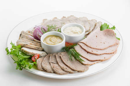 Sliced meat plateau ham with sauces and salad on white plate