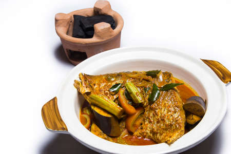 Curry of fish head with eggplant and traditional charcoal grill on white background