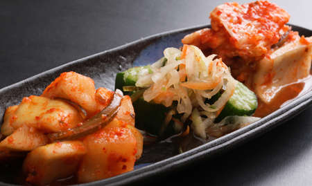 Kimchi Assorted with fermented radish and cucumber on black platter Stock Photo