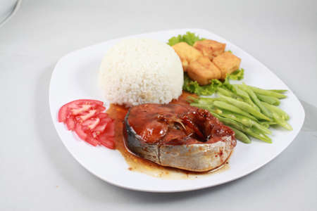 catfish: Plain rice with braised loin on catfish, fried tofu and boiled green bean on white plate in Mekong delta
