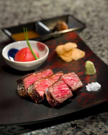 맛있는 볶은 철판 구이 일본 야에 야마 와규 쇠고기와 사비와 toamtoes 소스 검은 플래터에