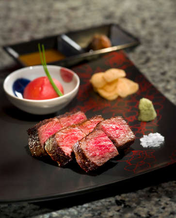 Delicious roasted Teppanyaki Japanese Yaeyama wagyu beef with wasabi and toamtoes sauce on black platter