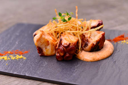 korean salad: Hot Tapas of fried octopus with sauce on black rock plate