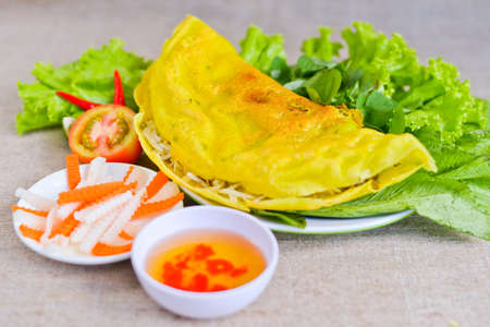 Vietnamese rice pancake with fish sauce, tomato and fermented carrot