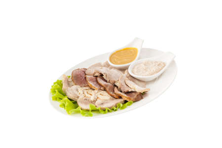 Bolied pork meart with lettuce and sauces on white plate
