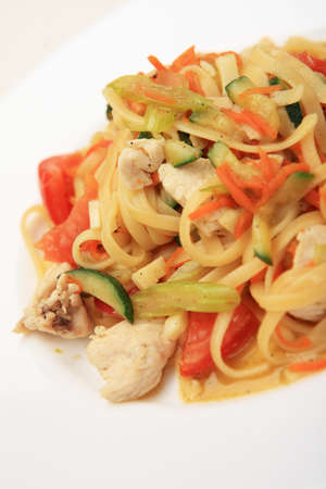 Linguine with chicken breast and vegetables on white plate