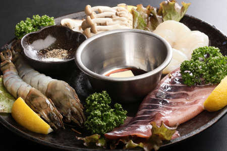 Seafood hot pot with fresh raw shrimp, squid, scallop, lemon, cumin, lettuce and mushroom on big black platter