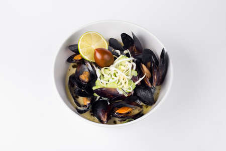 sopa: Blue mussels in a creamy sauce with lemon and olive in white bowl Stock Photo