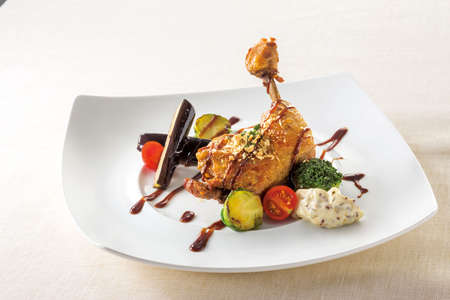 Confit beef curry sauce of bone in chicken thigh on white plate background