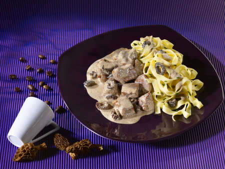 Veal with morel sauce on black plate on blue background