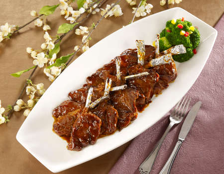mutton chops: Wine fried lamb cutlets on white plate in restaurant Stock Photo