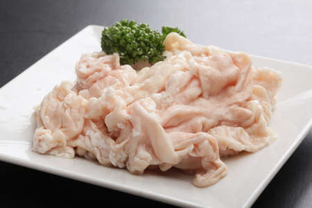 chitterlings: Fresh raw Pig hormone stomach with cumin herbs on white platter Stock Photo