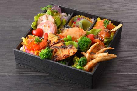 구운 생선, 연어 알, 죽순, 무, 토마토, 돼지 고기, 나무 테이블에 양상추의 Bento 식사 스톡 콘텐츠