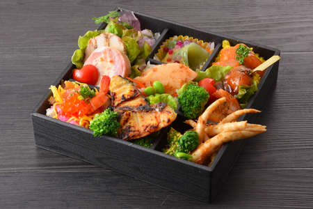 Bento meal of grilled fish, salmon eggs, bamboo shoots, radish, tomatoes, pork and lettuce on wooden table