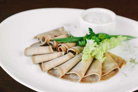 Sliced pork meat with lettuce on white plate in restaurant