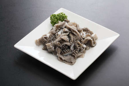 chitterlings: Baked omasum cow stomach with cumin herbs on white platter