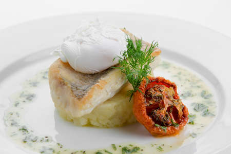 Sudak fried with crushed potatoes and poached egg on white plate