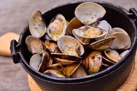 아시아 식당에서 나무 쟁반에 검은 냄비에 마늘 화이트 와인 조개 스톡 콘텐츠