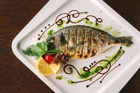 fish plate: Fried snapper fish with lemon and herbs on white plate