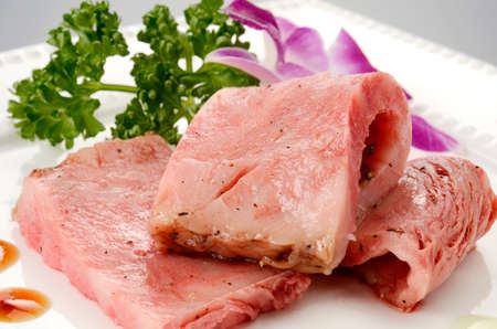 Fresh roasted beef on white plate with herbs in restaurant