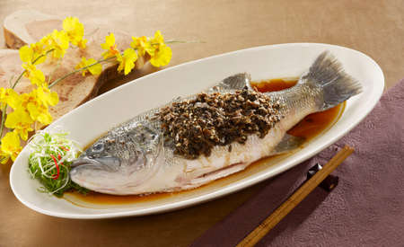 Meicai steamed fresh water fish grouper with sauce on white plate