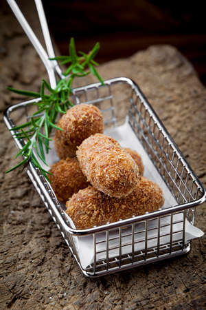 Special fried Jamon Iberico Croquette in iron basket with rosemarry