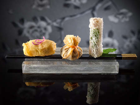 Fried Dim Sum and spring rolls with chopsticks on platter