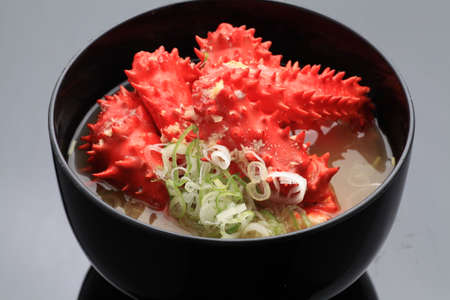 Big bowl of snow red King crab legs soup with onion and miso