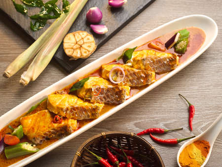 rajma: Asam Fish curry with garlic, chili, lemongrass, onion and sauce on wooden table