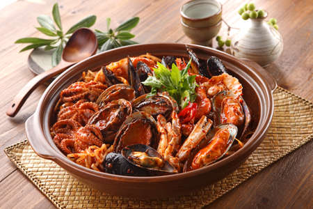 Steamed kimchi seafood with abalone, blue mussel, octopus, crab and herbs in big bowl on wooden korean table