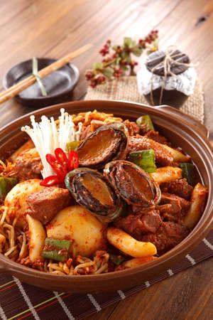 Big bowl of kimchi lunch with abalone, mushrooom, potatoes, beef and noodle on wooden korean table Stock Photo