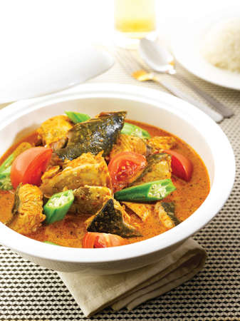 Curry Fish Head with tomatoes and herbs in white big bowl on the table Stock Photo