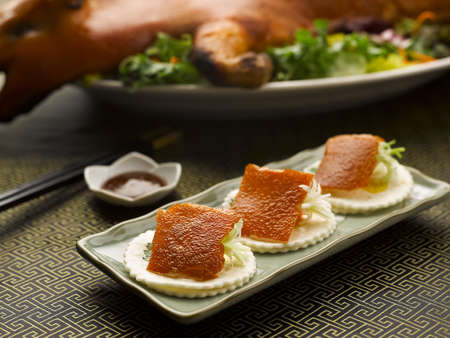 spanferkel: Roasted Suckling Pig skin with onion and crackers on dish in restaurant