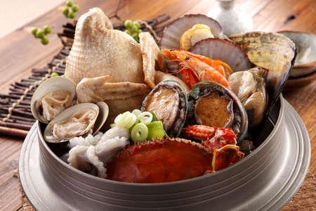 나무 한국어 테이블에 신선한 낙지, 전복, 게, 조개, 새우, 닭고기와 바다의 당나라 황제의 큰 냄비